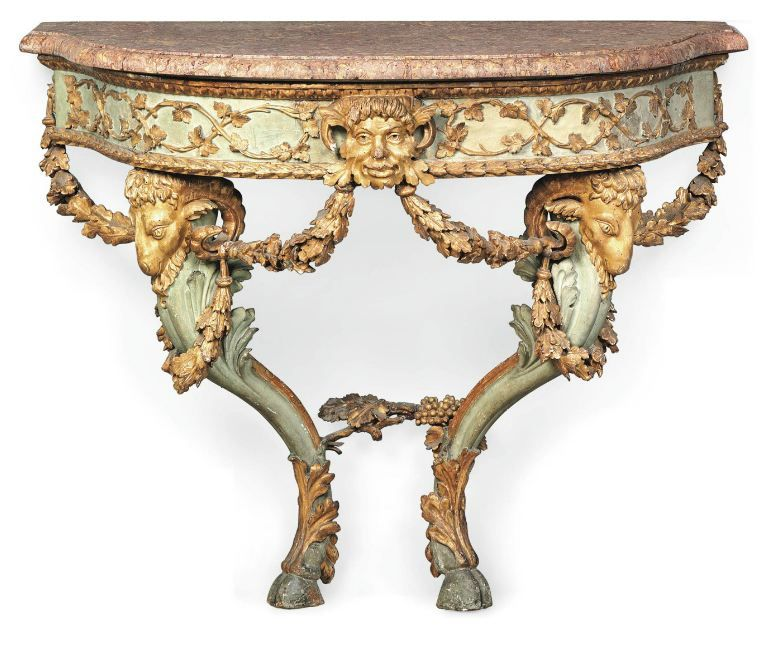 A North Italian giltwood and green painted console table. With a shaped violet Jura brocatelle marble top above an entwined foliate frieze centred by a Satyr mask issuing laurel swags, supported by rams' head monopodia terminating in cloven feet.