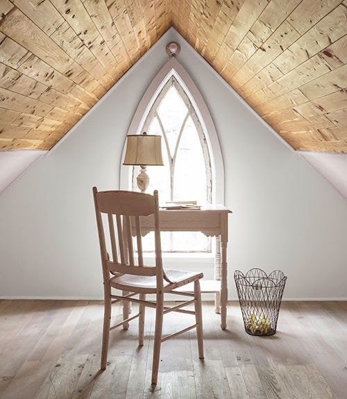 tidy little desk tucked into a Gothic arched window triangulated by the abrupt angles of the ceiling and walls-