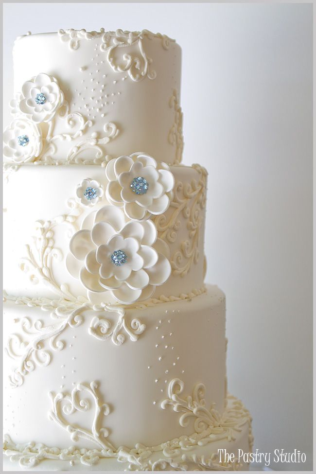 a glamorous wedding cake with handmade sugar paste flowers, using Swarovski crystals