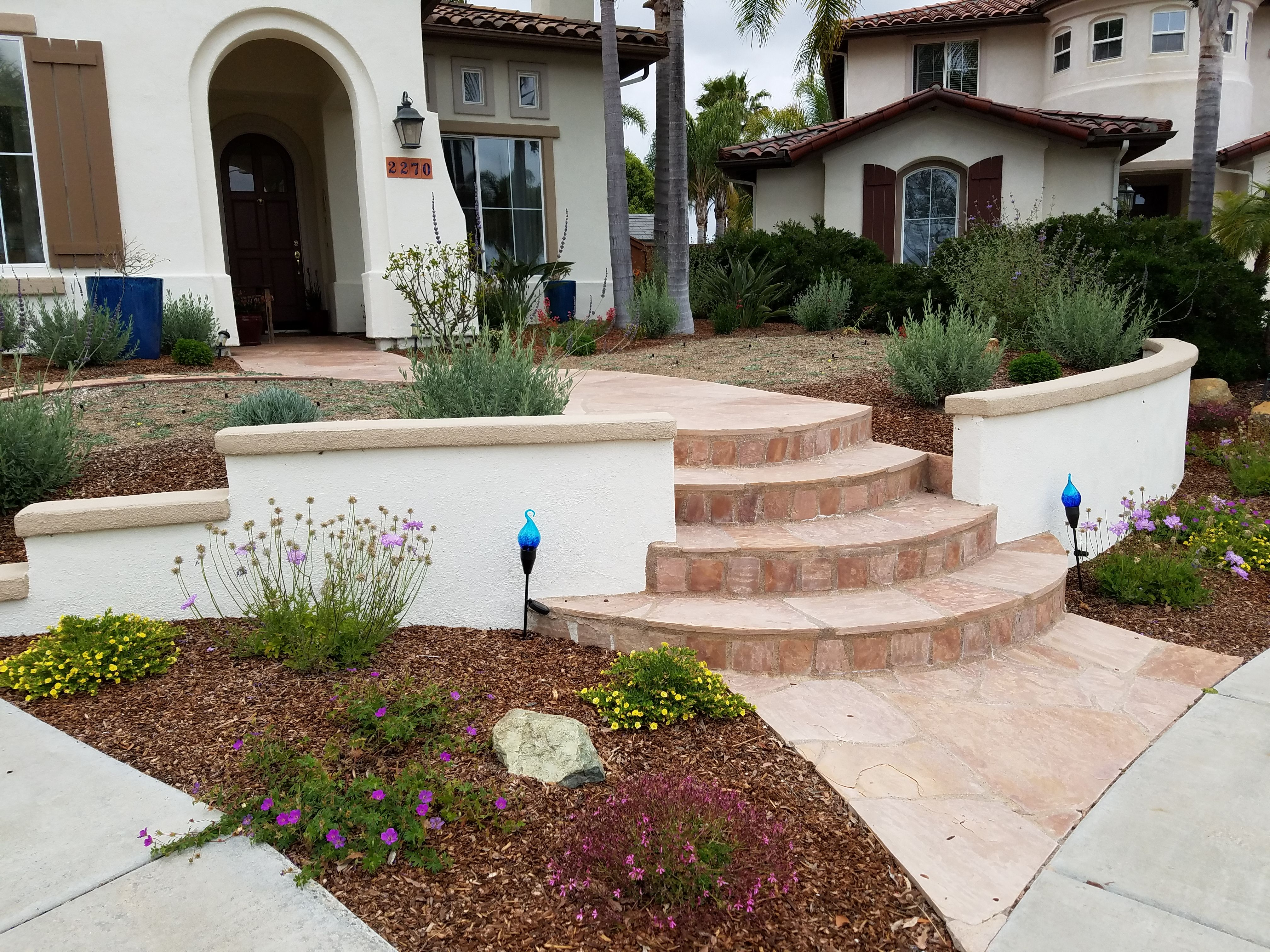 Front Entry With Low Wall Stucco Wall And Curved Flagstone Walkway
