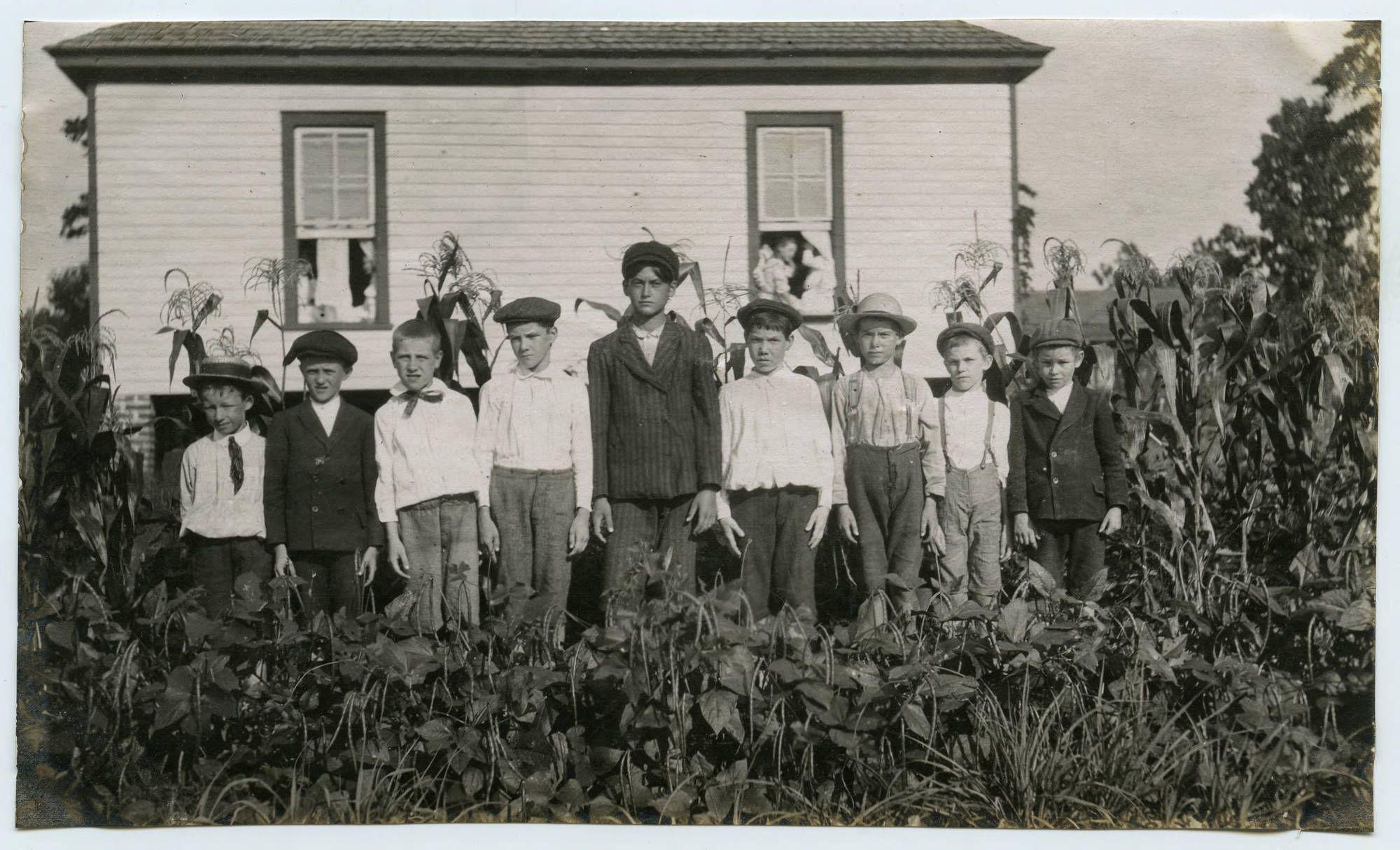 A group of nine boys, student age, pose in a garden, circa 1900s.