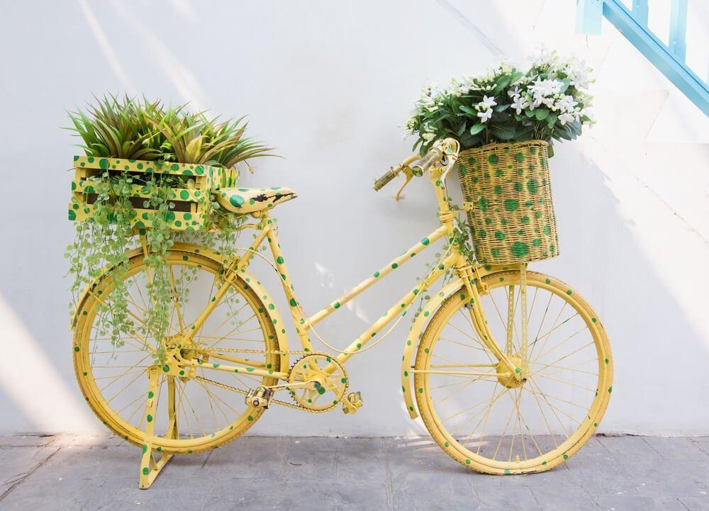 Gelb-Bike mit grünen Polk a-Punkten mit Blume-Pflanzer (Korbweide und rot) auf der Vorder- und Rückseite.