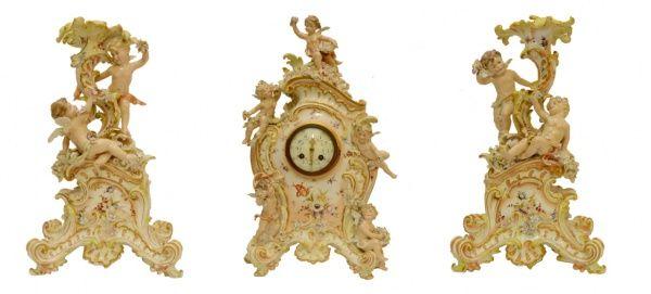 Terno de porcelana alemã composto de relógio central e par de castiçais. Decoração em ouro caracterí