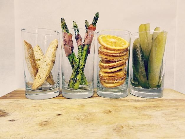 Sunday Brunch Cocktail Mise in Place-Housemade Biscotti, Grilled Prosciutto Wrapped Asparagus, Candied Orange Wheel, Housemade Gherkins