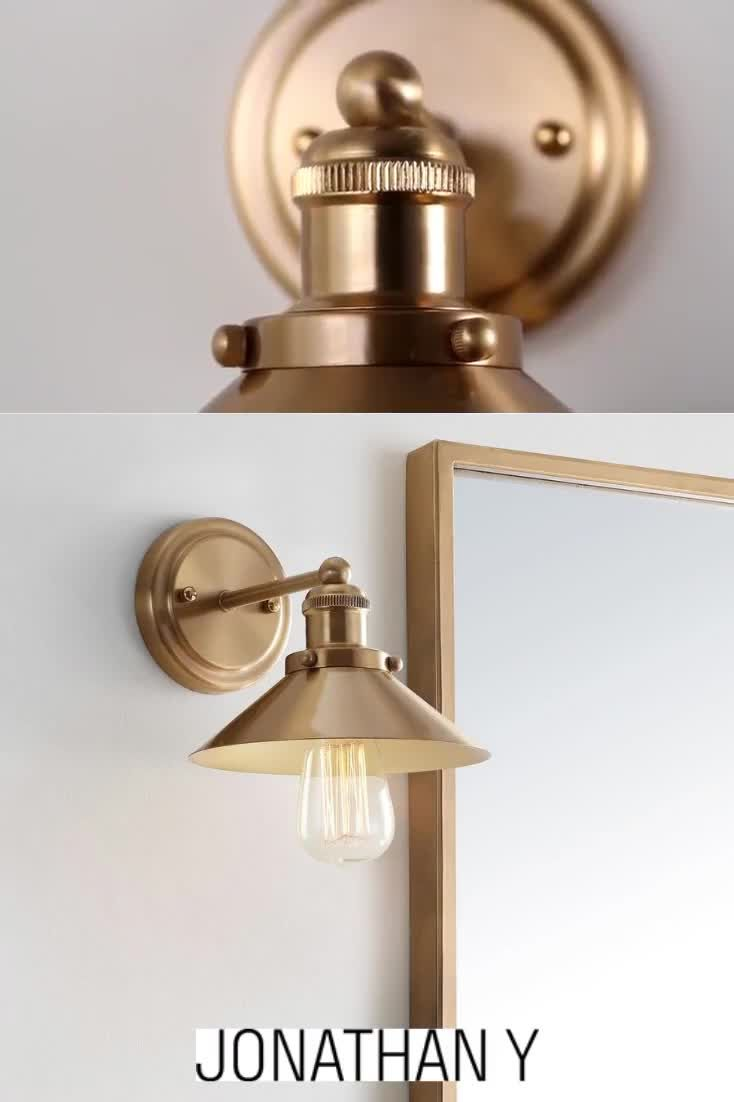 Drive the vintage feel in your space with this wall sconce finished in brass gold. A metal cone-shaped shade leaves part of the bulb exposed for a stunning look while providing ample brightness to your space. Metal construction adds to the smooth, industrial look while ensuring durability, and the compact size makes this wall sconce easy to fit into your room. #JonathanY #HomeDecor #Lamps #DesignerLamps #ModernLighting #sconce