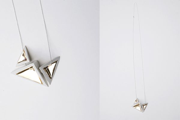 Aster is a ceramic necklace with a minimal design consisting of three tetrahedra hand painted with gold backed at 700 degrees, mounted on silver chain.