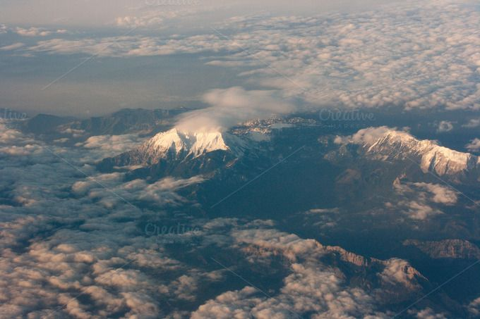 Mountain ridge peeking trough the clouds, shot taken from an airplane.