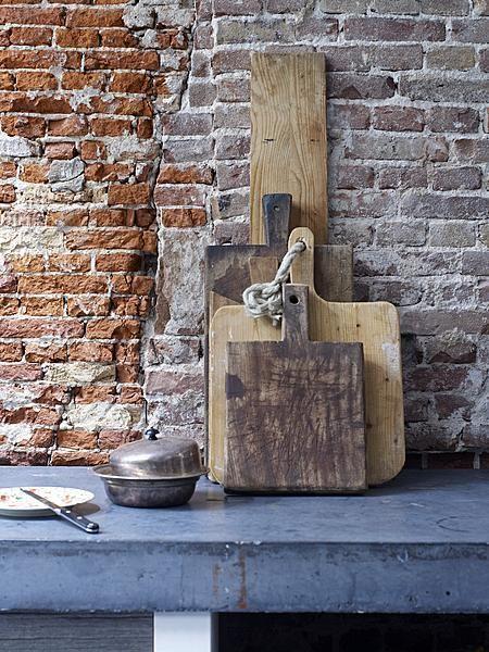 Door harde (steen, beton) en zachte (hout) materialen te mixen verveelt deze keuken nooit.