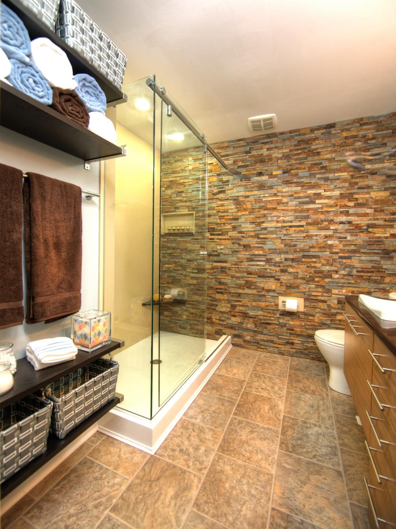 A wall of stacked stone continues into the glass-enclosed shower ...