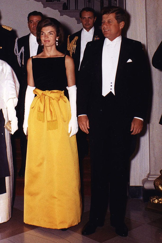 COLOR-BLOCK WITH SEPARATES A gown for a black-tie affair? . Jackie pieced together a stunning look, color-blocking with a black square-neck top, a sweeping marigold yellow ball skirt, and white bicep-high opera gloves.