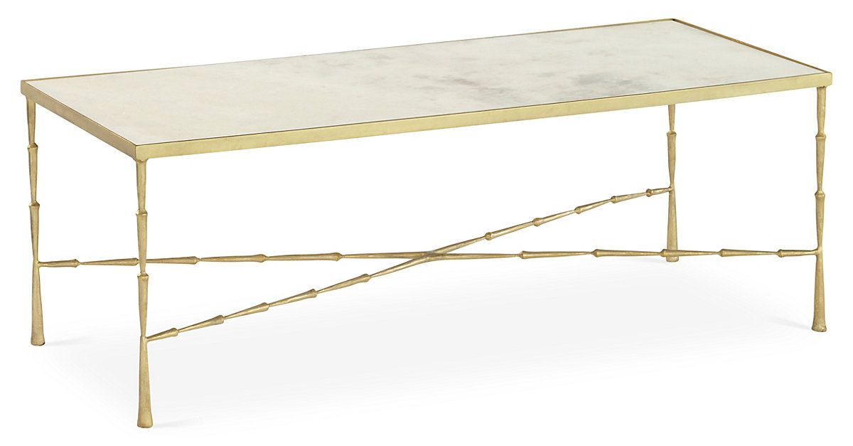 This cocktail table pairs a beautifully crafted iron frame with an inset marble top. A luxe gold finish completes the look.