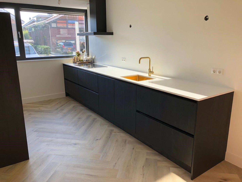 Zwarte hout look keuken gecombineerd met een wit marmer look