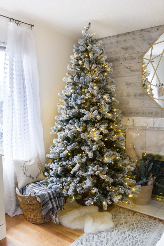 a flocked tree decorated with only lights for those who want - simple christmas tree decorating ideas