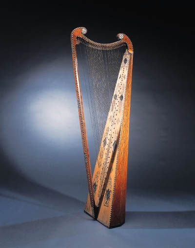 A CROSS-STRUNG HARP  Probably 19th Century in the 17th Century Italian style  The back of seven staves with geometric decoration, the column, arm and soundboard edged with alternating ivory and ebony lozenges, the arm and soundboard terminating in decorative finials set with ivory, the soundboard set with seven soundholes with elaborately carved roses with ivory and ebony inlay  61.5/8 in. (156.5 cm.) high