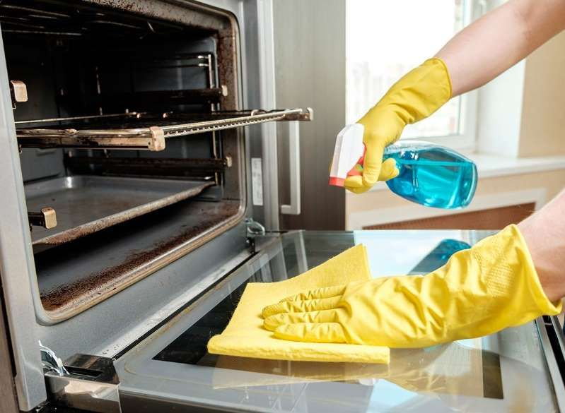 a person cooking in an oven: Hands cleaning oven | Oven ...