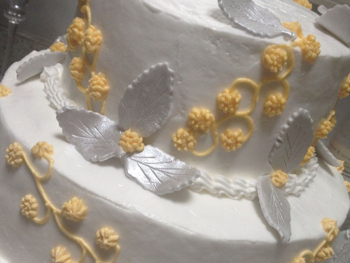 Wedding cake with hand painted silver leaves and yellow flowers