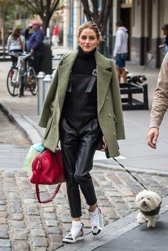 Olivia Palermo looked so chic in black leather overalls, a green pea coat, sneakers, and a red bag.