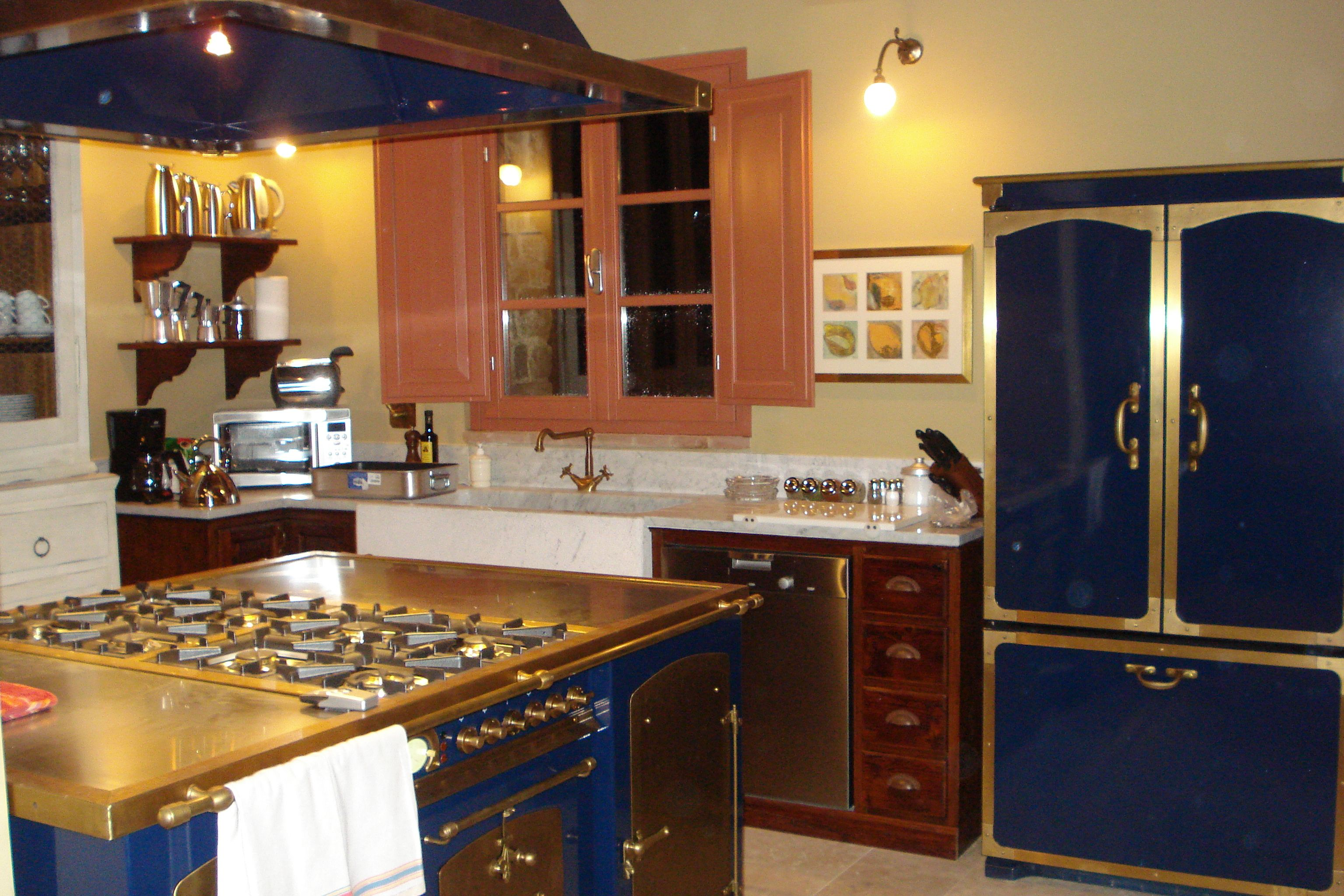 Italian casita farmhouse kitchen with navy and gold appliances