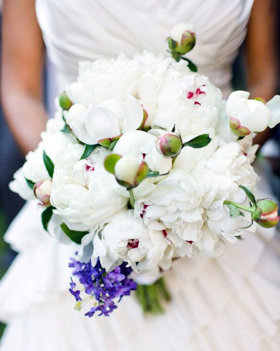 """Black Iris finished off the bride's peony bouquet with a sprig of lilac in remembrance of her grandmother who always had the most beautiful lilac bushes in front of her house. A vintage brooch found by the bride and her sister while antique shopping was added to the bouquet's stems and served as her """"something blue."""""""