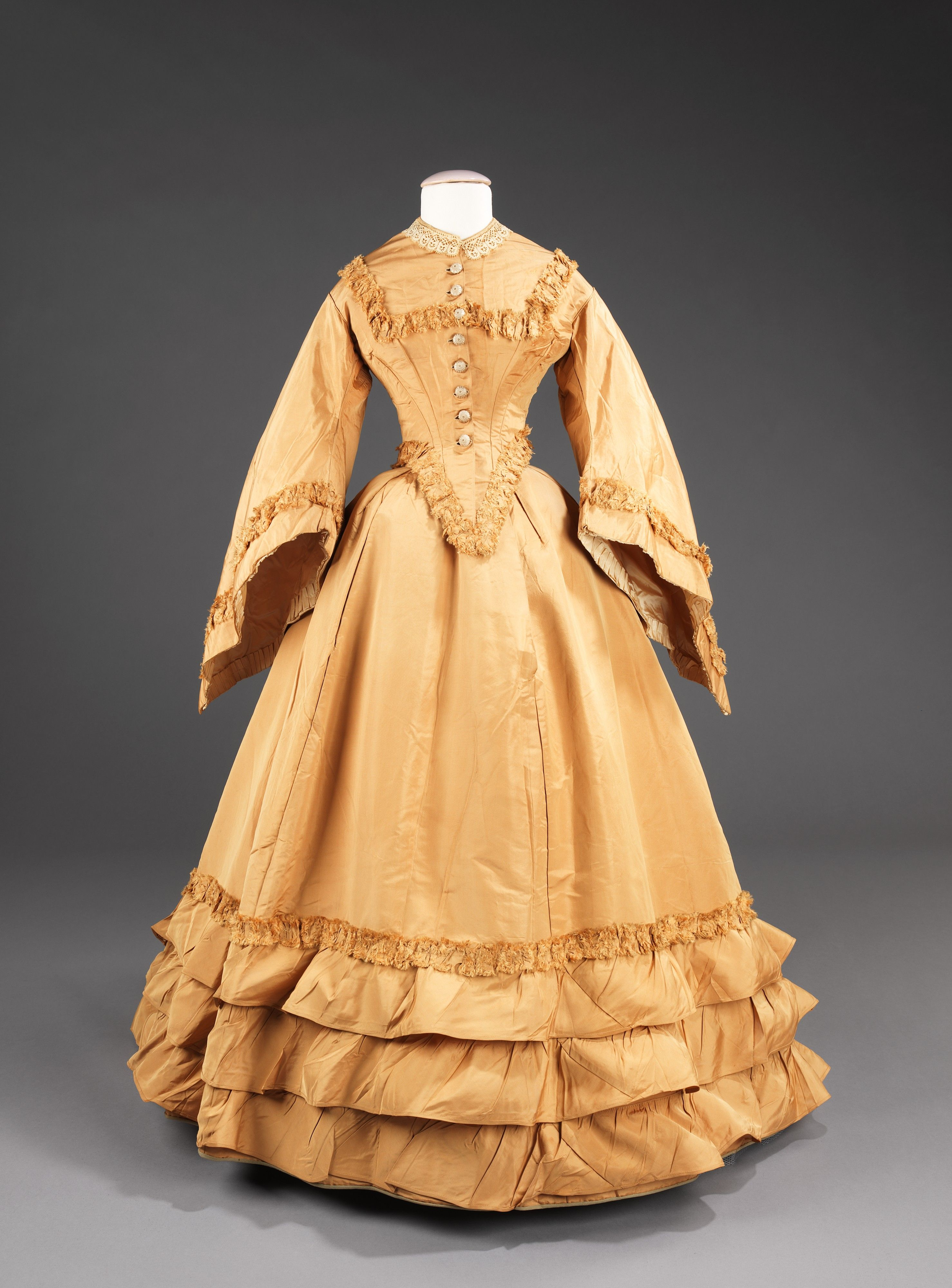 This wedding dress presents a conundrum in that some stylistic aspects of the dress appear to be later than the marriage date of 1851 provided in the original accession records.   While the bodice has very fashionable full size pagoda sleeves, which were a new shape in 1851, the skirt with bustle, train and ruffles at bottom is more consistent with the 1870s rather than the dome shape of the 1850s