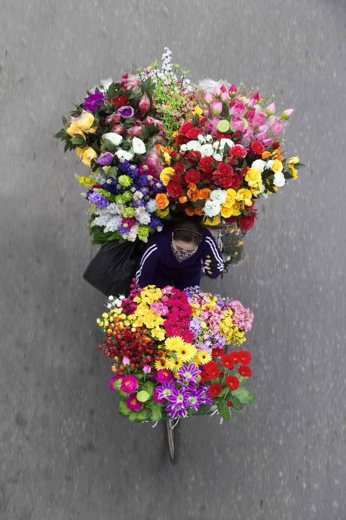 """""""A vendor selling silk flower is cycling quite fast. Not all vendors can cycle on their cycle. Some use the seat for storage, and other cycles are too heavy"""" 