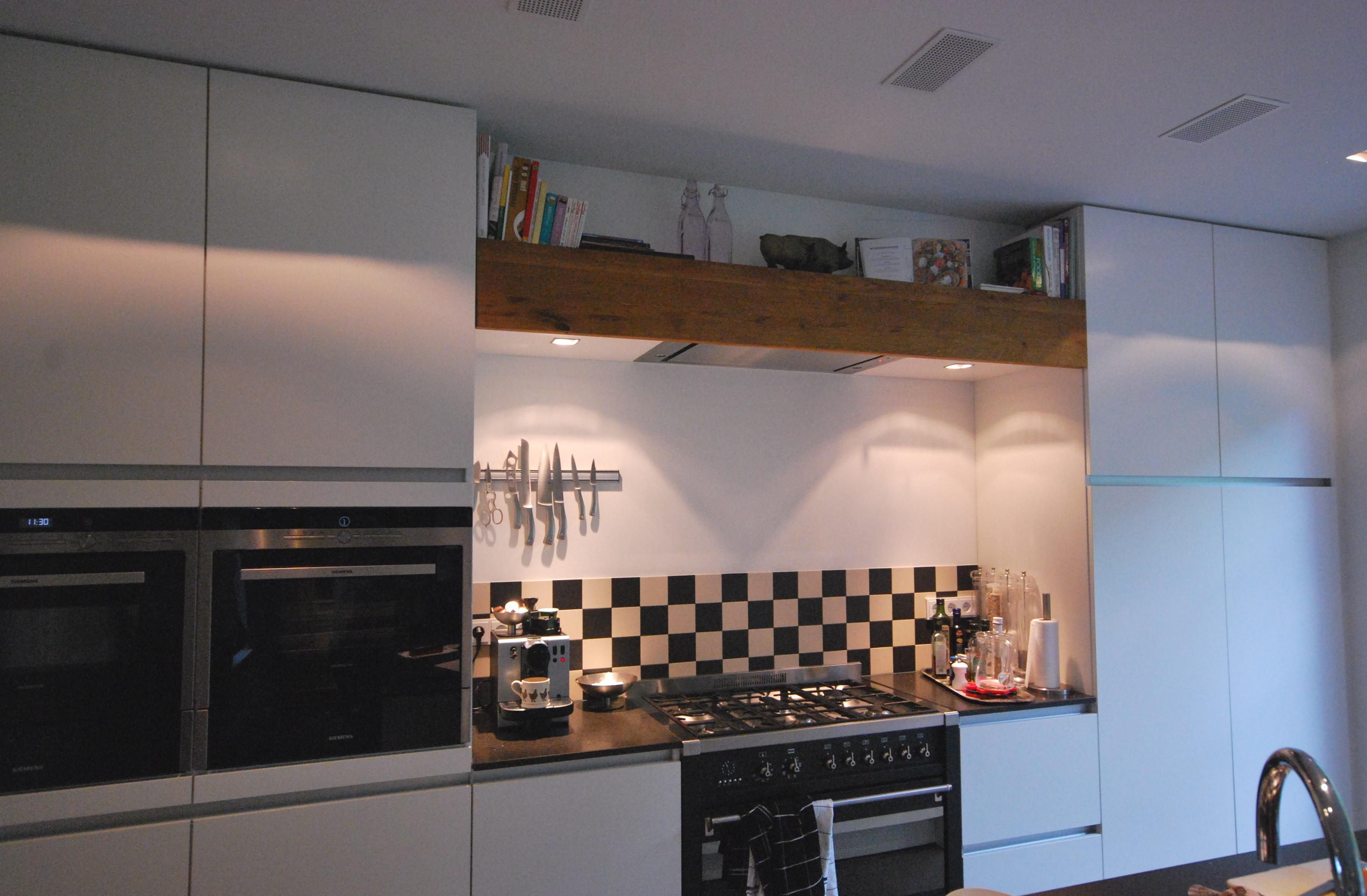 Moderne mat witte greeploze woonkeuken met fornuis van smeg