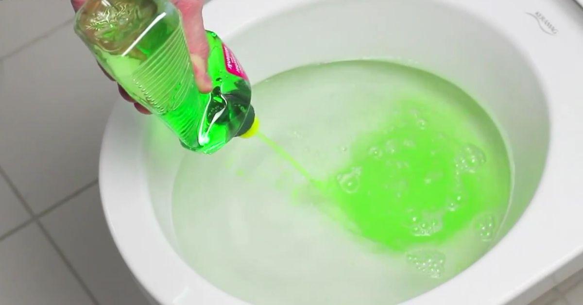 Ein Handwerker schüttet Spülmittel ins WC. Was das bewirkt