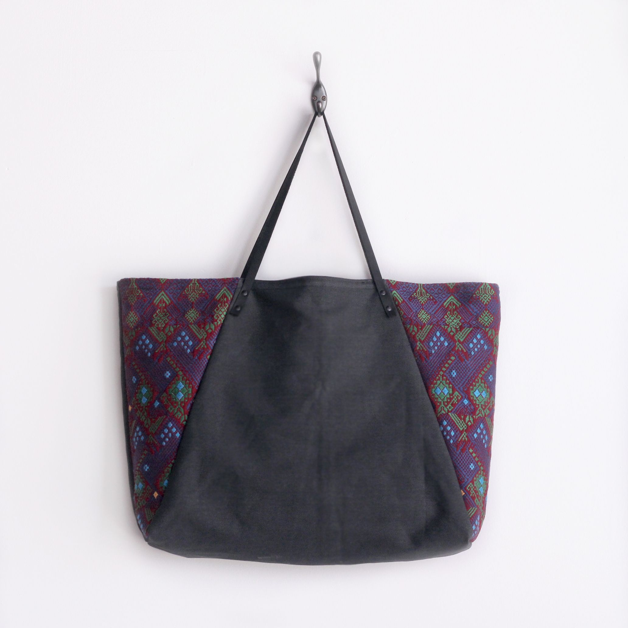 anne b designs and WILCOX Boots brings you a collection of classic bag silhouettes with a taste of authentic textiles from Guatemala Don't be fooled by it's elegant appearance, but just like WILCOX leather boots, this durable canvas tote can take on a full days work. The Guatemalan textile makes a stunning statement against the charcoal gray canvas exterior. Lined with camel tan, 2 pockets that extend the full length of the tote, and an additional splash of Guatemala on an inter...