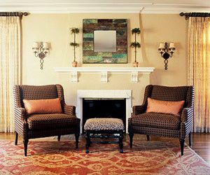 Two Arm Chairs In Front Of Fireplace On A Red Rug