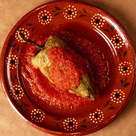 """Traditional pork filled """"chile relleno,"""" or stuffed pepper in salsa roja."""