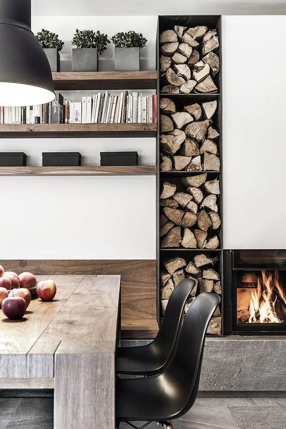 a built in fireplace and built in firewood storage next to ...