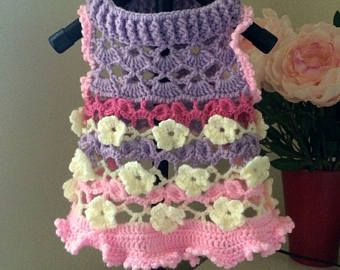 Crochet dog sweet dress in pink and purple color with 3D white flowers.