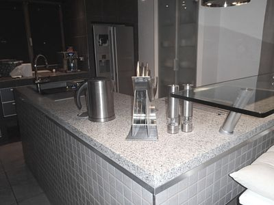 Žulovou pracovní desku na kuchyňském ostrůvku doplňuje mozaika, jíž je ostrůvek obložen. U spotřebičů a dalších prvků vsadila majitelka na nerez.