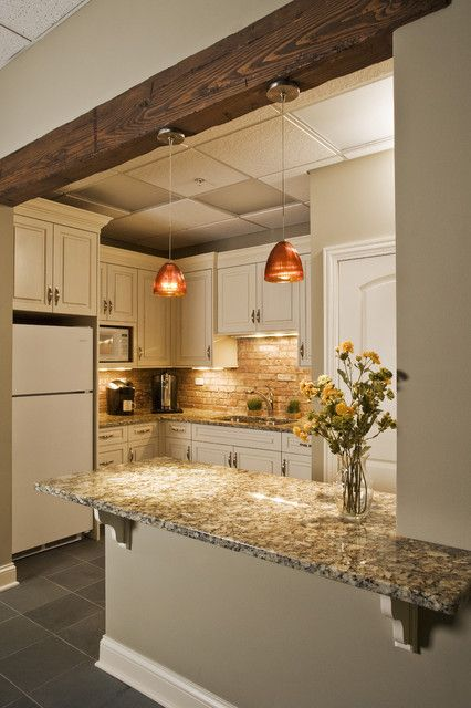 Kitchenette with wooden beam in entryway and brick backsplash