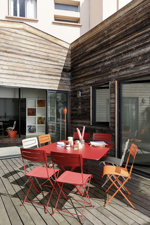 terrasse avec table cargo chaises slim et torches de jardin