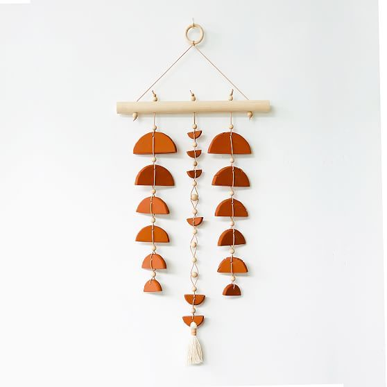 West Perro uses clay, wood, cotton and natural leather to craft lifestyle goods that are inspired by the natural shapes, colors and textures of the desert. The Sonoran Sunset Wall Hanging was influenced by evening sunsets, lunar moon phases and rare solar eclipses. Created by West Perro. Learn more. Approx. 16