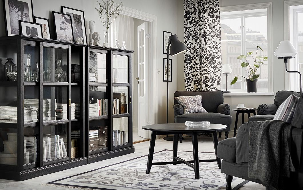 A Living Room Furnished With Dark Grey Armchairs, A Black Coffee Table And  Two Black Glass Door Cabinets With Sliding Doors.