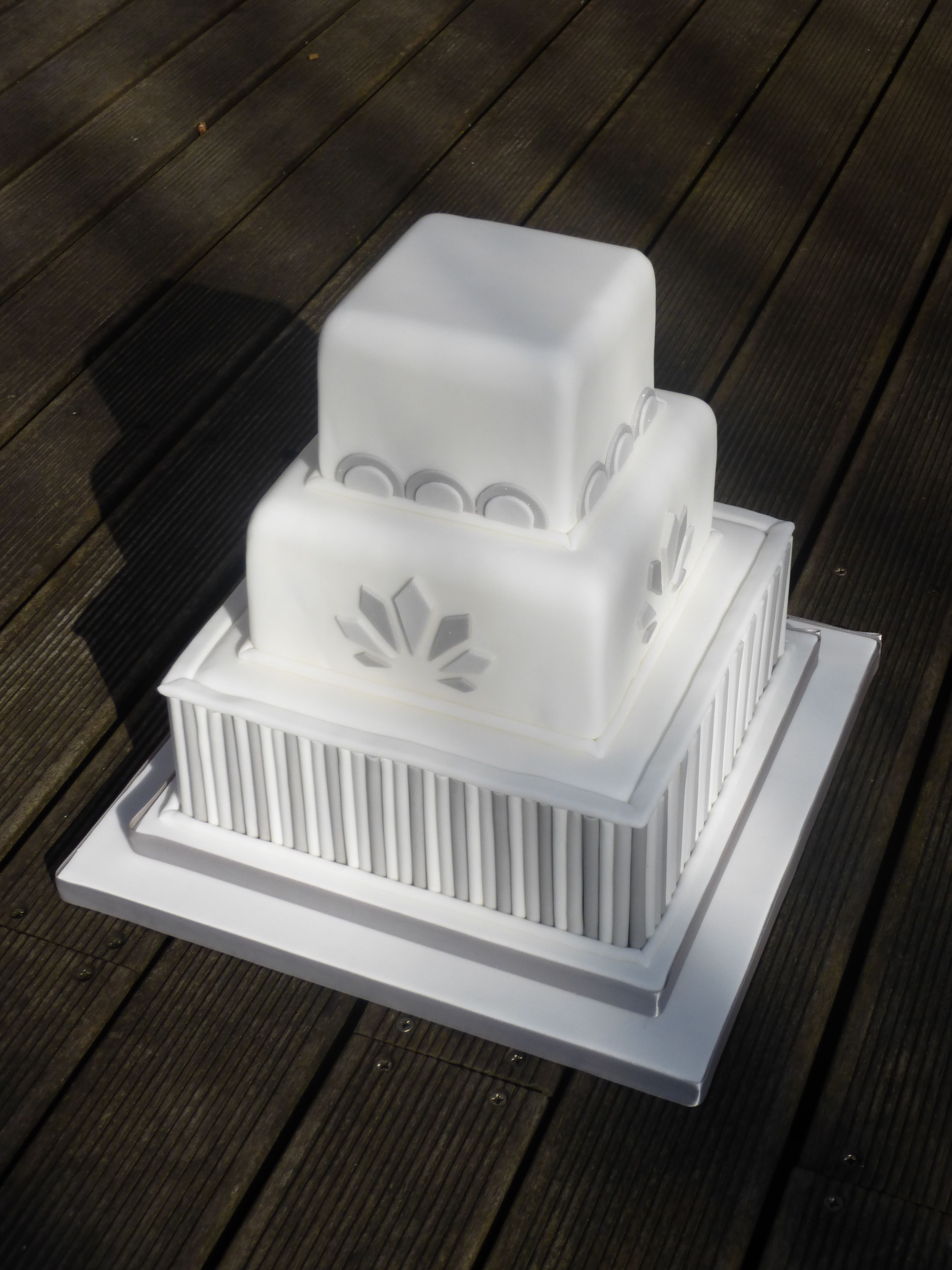 An Art Deco inspired wedding cake in white, pale grey and dark grey ...