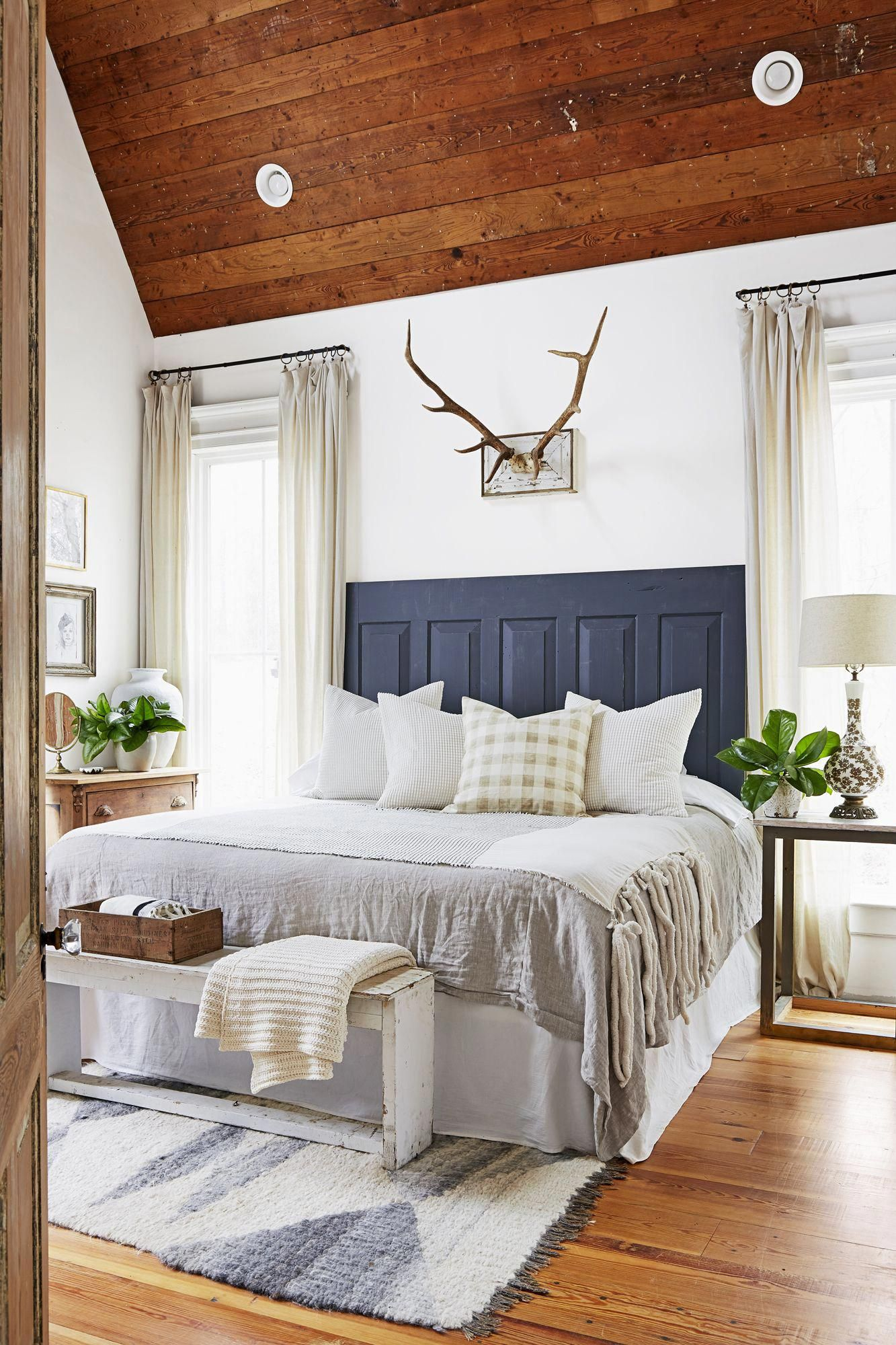 Master Bedroom With White Walls Wood Ceiling And Navy Headboard Farmhouse Style Master Bedroom Master Bedrooms Decor White Wall Bedroom
