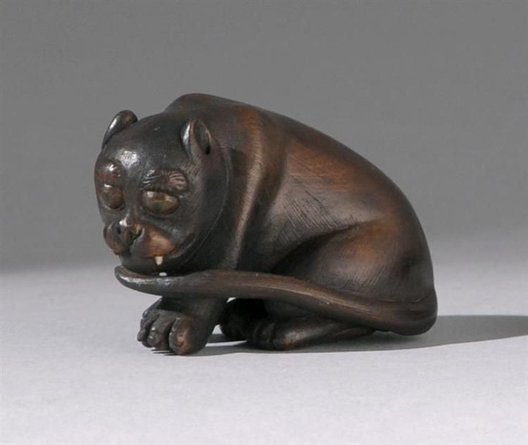 WOOD NETSUKE 19th Century By Tomokazu. Depicting a seated tiger with inlaid eyes…
