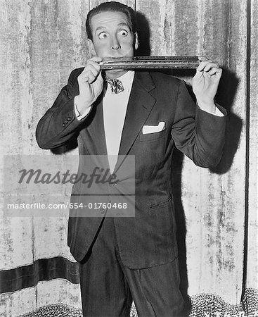 Masterfile's licensor warrants that no model release is required for this image - Portrait of man playing huge harmonica  – Imagem © Masterfile.com: Fotografias, vetores e ilustrações criativas de arquivo para sites, telefones celulares e impressão.