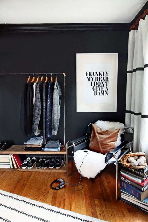 Minimal Bedroom With A Modern Black Chair, A Lamb Throw, And A Rolling Rack