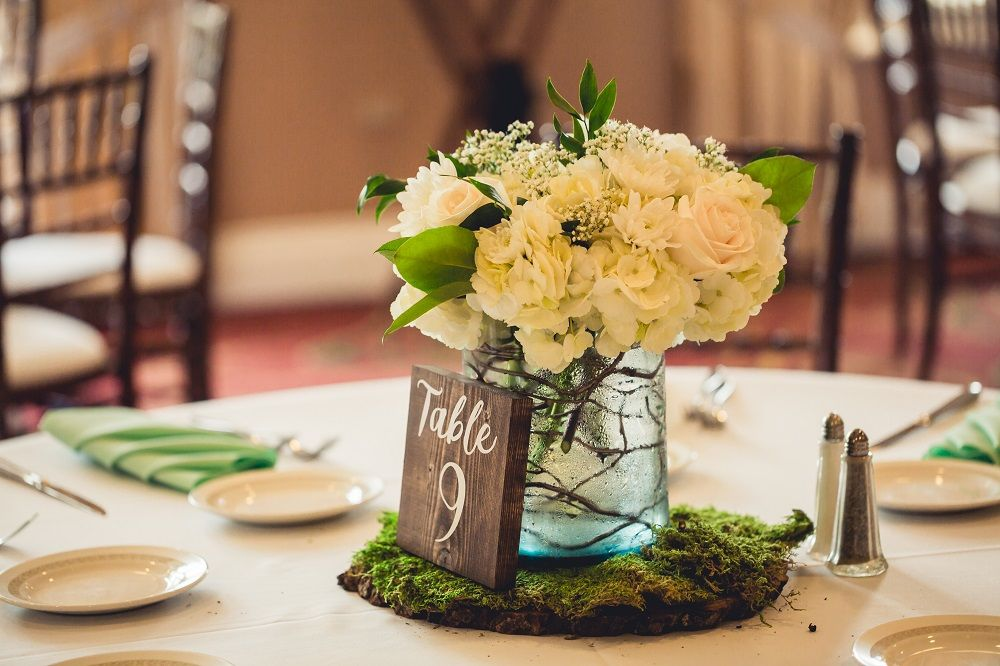 Low Vase Centerpieces On A Wood Slice With Moss Give A Natural Feel Moss Centerpieces Mason Jar Centerpieces Rustic Centerpieces