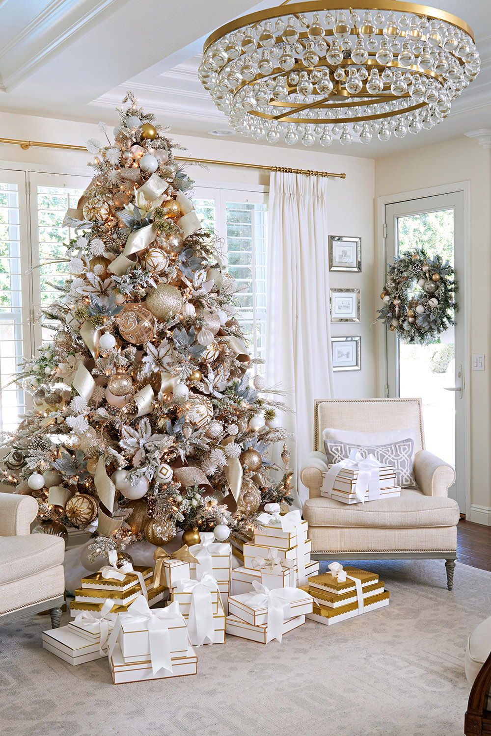A soft flocked Christmas tree anchors this luxe holiday living room. Enhance it with faux flower blooms, ribbons, and loads of ornaments. Gift boxes, rather than paper wrappings, coordinate with the decor's color scheme. #livingroomdecor #christmaslivingroomdecor #holidaylivingroomdecor #christmasdecorideas #christmasdecorideasforlivingroom #bhg