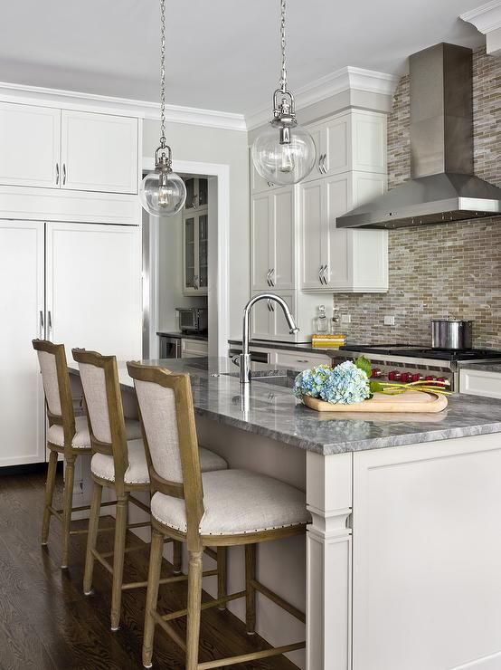 Superb Two Clear Glass Globe Lights Hang Over A Light Gray Kitchen Island Accented  With Legs Topped With Charcoal Gray Stone Fitted With A Stainless Steel  Sink And ...