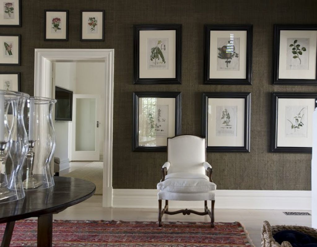 Foyer decorated with grasscloth wallpaper and framed wall pictures