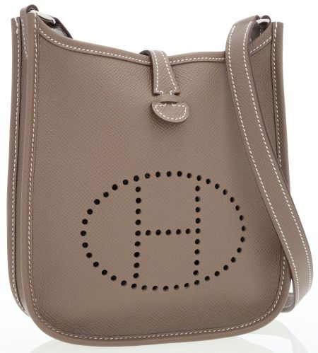 d29bf56237a The exterior of this beloved Hermes Evelyne miniature crossbody bag is done  in Etoupe Epsom leather