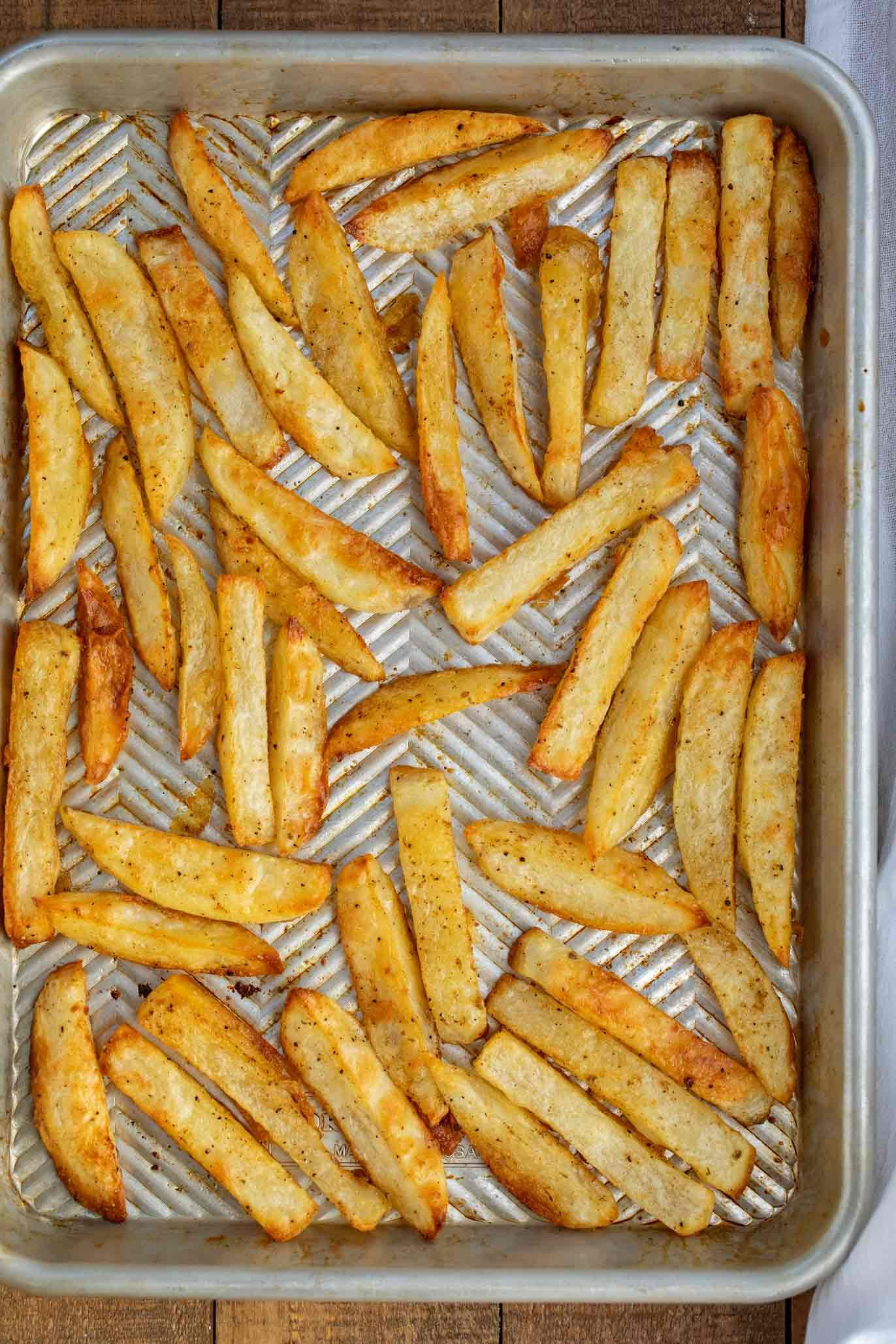 Baked French Fries are russet potatoes lightly coated with olive oil and seasoning and baked until they're warm and crispy, ready in under 45 minutes! #potatoes #fries #frenchfries #homemade #crispy #garlicfries #dinnerthendessert #russetpotatorecipes