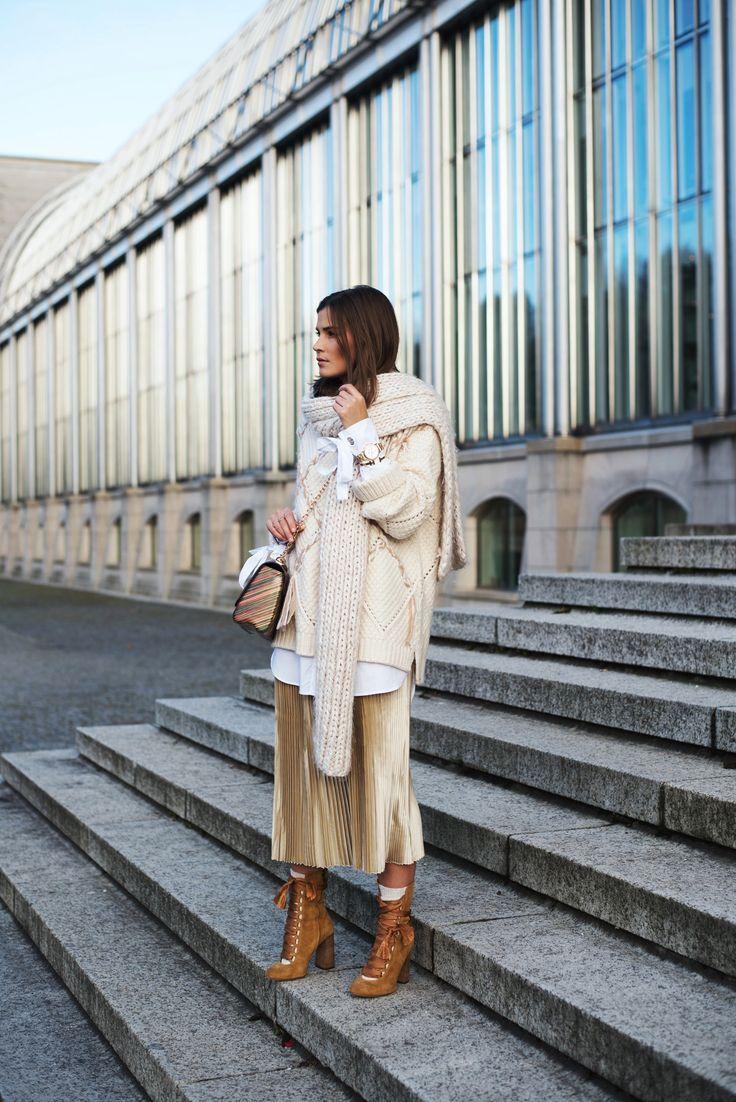Nina Schwichtenberg trägt einen winterlichen Layering Lock, bestehend aus Plissé Rock, langer Bluse und Pulli. Dazu kombiniert sie die Chloé Harper Boots, die Louis Vuitton Twist und Schmuck von Tommy Hilfiger. Mehr auf www.fashiioncarpet.com