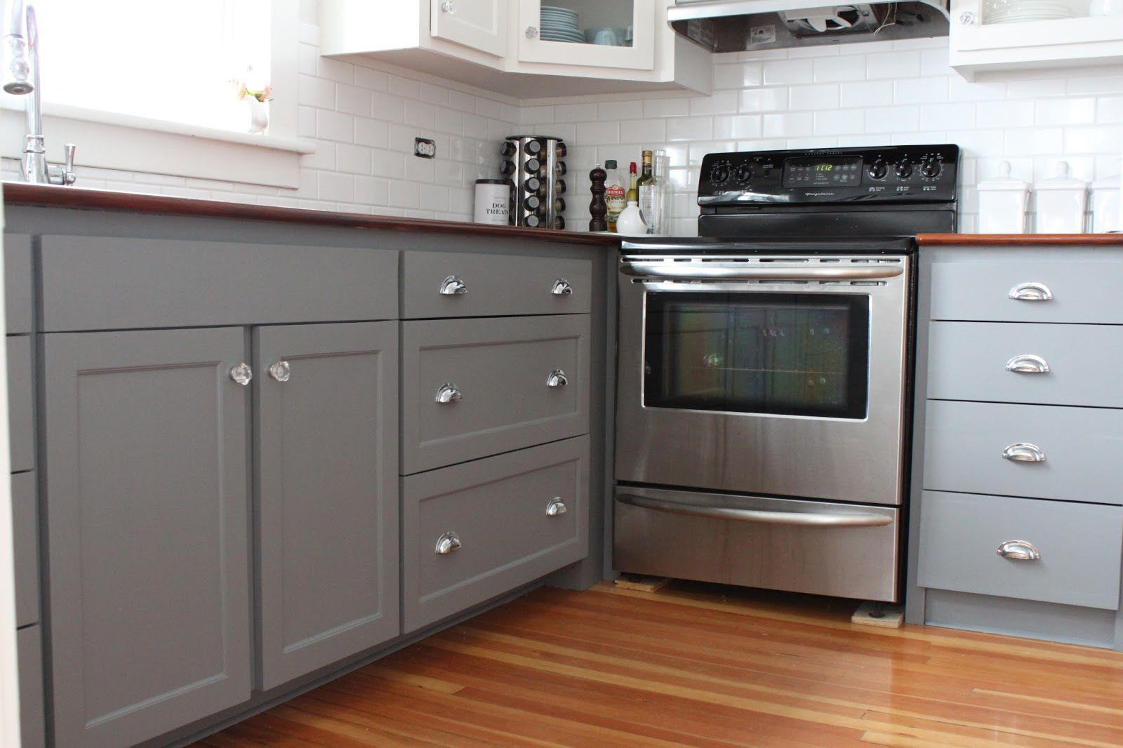 Gray Cabinets Paired With Marble Countertops And White Subway Tile